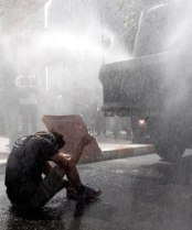 WATER BLAST: A demonstrator shelters as Turkish riot police fire a water cannon at protesters occupying a park in central Istanbul, injuring scores - http://www.stuff.co.nz/world
