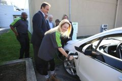 Brynn O'Reilley, a second year student in the Energy Systems Engineering Technology at St. Lawrence College plugs in an electric vehicle at the launch of the college's new charging station. (Elliot Ferguson The Whig-Standard)