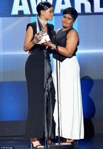 Rihanna receiving her AMA Icon Award from her mother.
