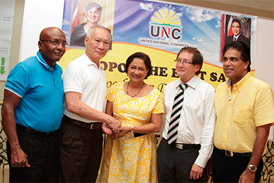 "Prime Minister Kamla Persad-Bissessar greets former Clico chairman Gerard Yetming, second left, and former Senate president Timothy Hamel-Smith, second right, after they showed up at a UNC ""foot soldiers"" mobilisation meeting in Debe on Tuesday. Also in photo are Oropouche East MP Dr Roodal Moonilal and UNC campaign manager Rodney Charles, left. PHOTO: RISHI RAGOONATH"