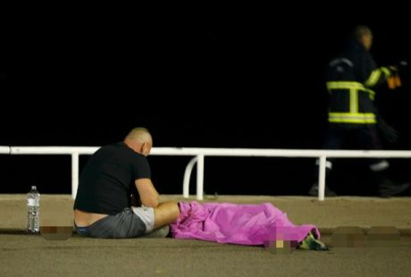 A man sits with a victim on the seafront